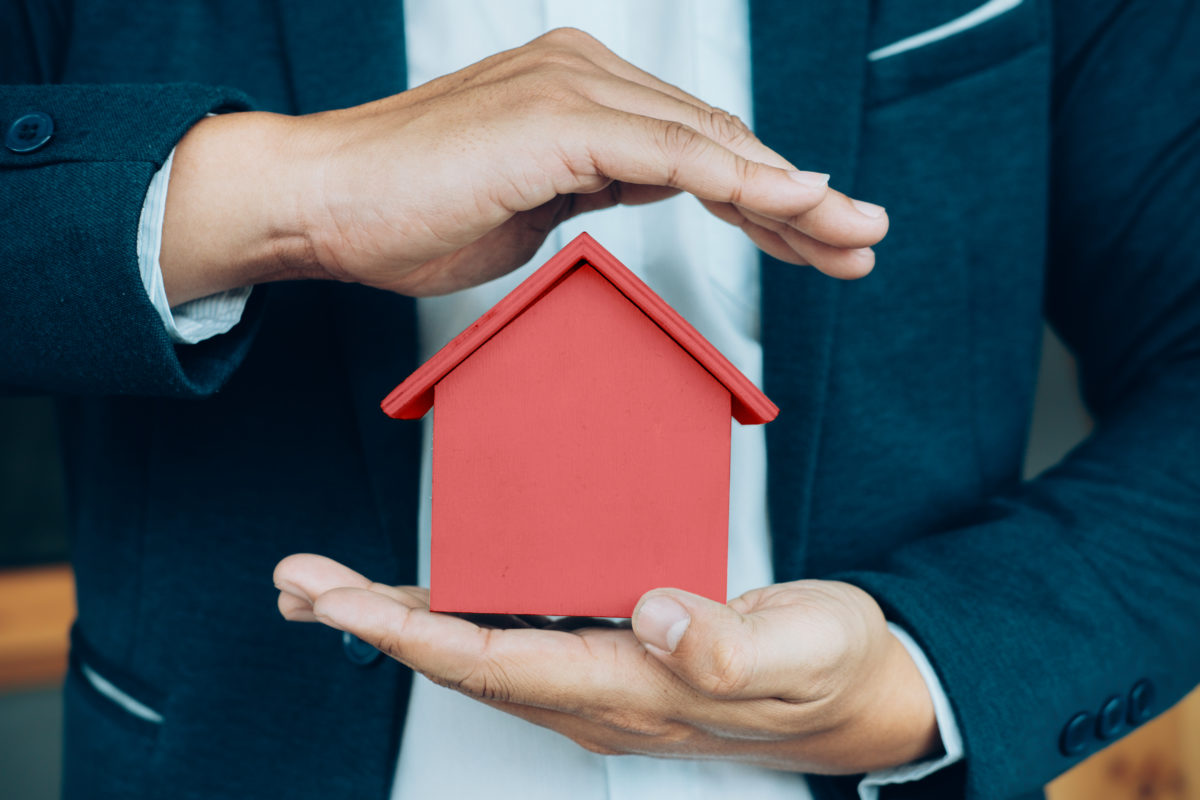 Business man hand holding a house model protecting house with title insurance for homeowners