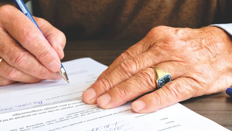 A man with a turquoise ring signing some paperwork.