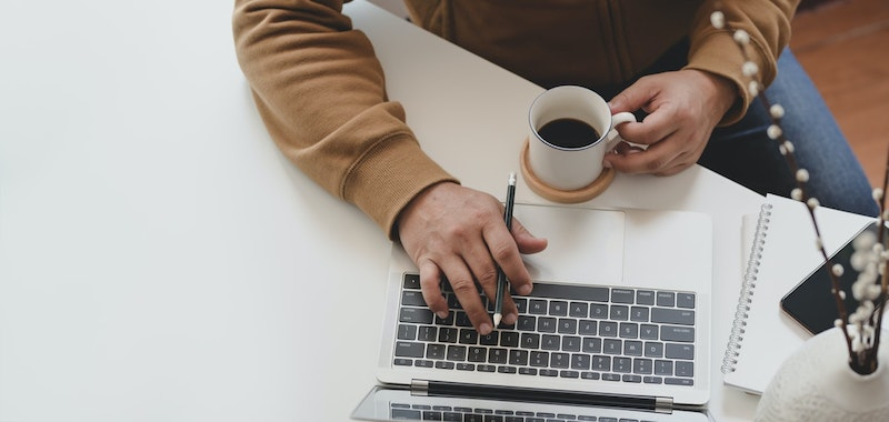 A person wearing a sweater with one hand on a computer keyboard and the other holding a small cup of coffee.